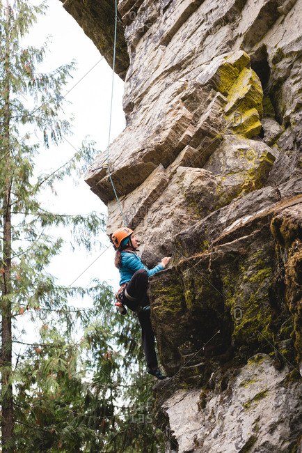 Determined female climber climbing the rocky cliff