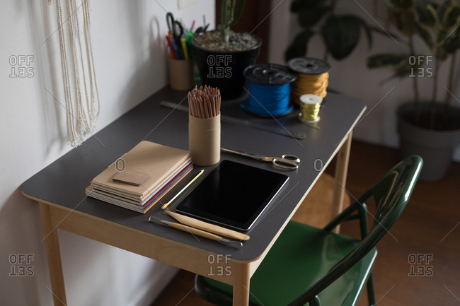 Digital tablet and stationery on table in workshop