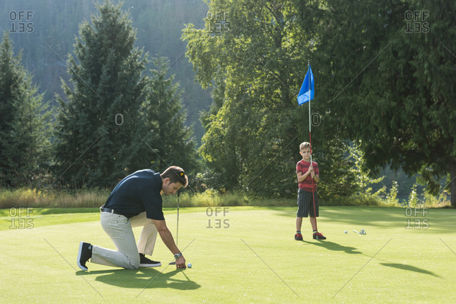 Father and son playing golf in the course