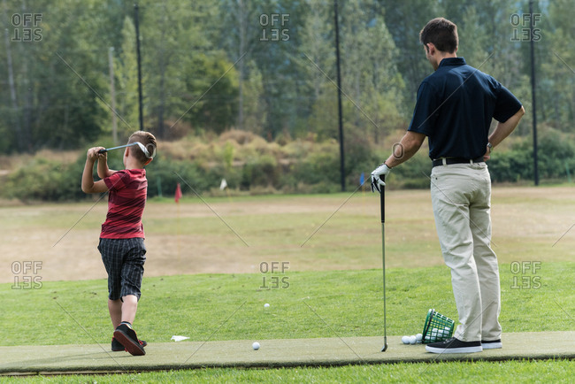 Father and son playing golf on golf course