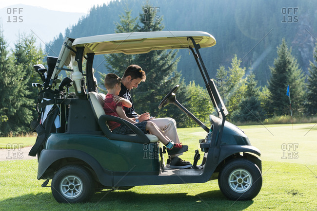 Father and son sitting in the golf cart on a sunny day