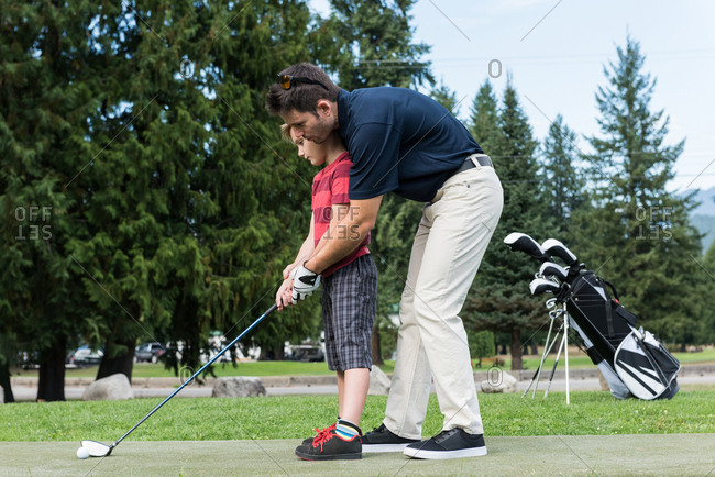 Father assisting his son to play golf in the course