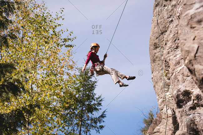 Female climber struggling up the rocky mountain on a sunny day