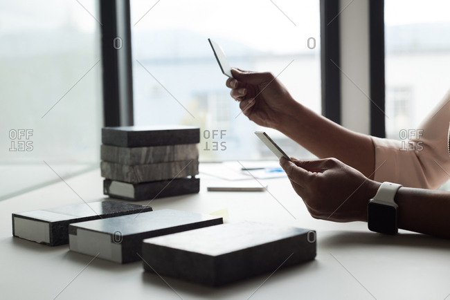 Female executive examining slabs at desk in office