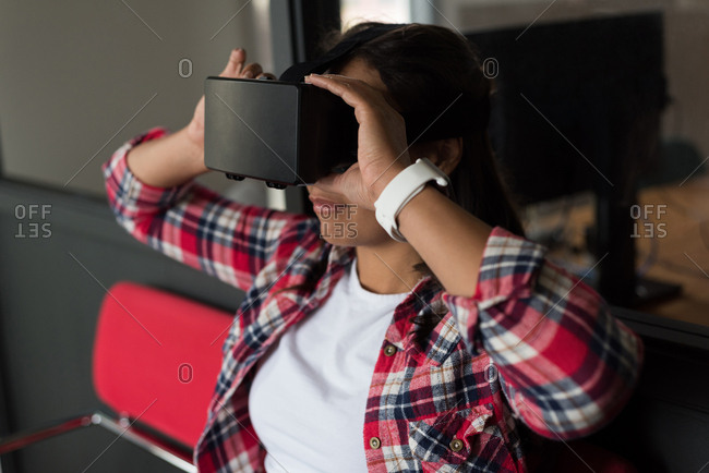 Female executive sitting on chair and using virtual reality headset in office