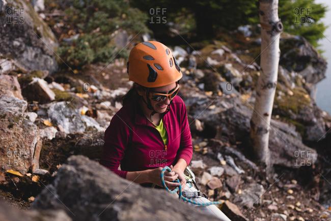 Female hiker preparing herself to climb the rocky mountain near lakeside