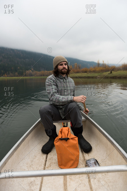 Fisherman oaring canoe in the middle of the lake