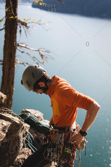 Hiker adjusting the carabineer with rope near lakesdie
