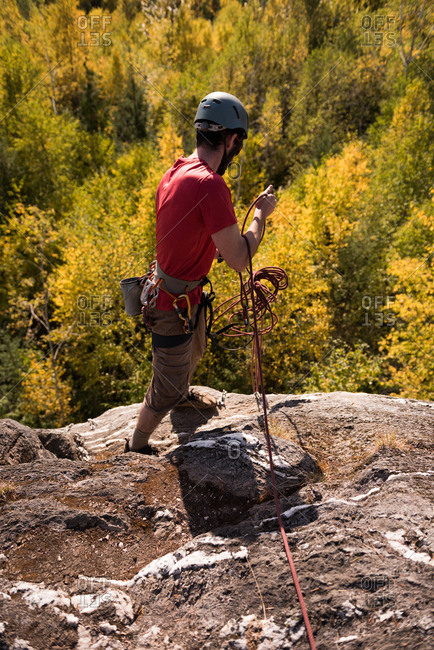 Hiker gathering rope while standing on the mountain in the forest