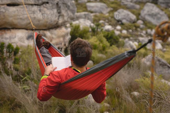 Hiker lying in hammock reading novel on a sunny day