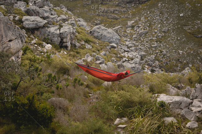 Hiker relaxing in hammock on a sunny day