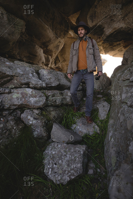 Hiker walking down on rocks in the cave