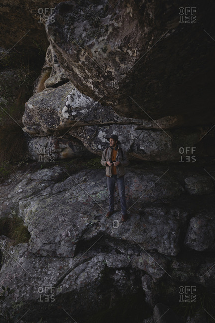 Hiker with binoculars standing on rock in the cave
