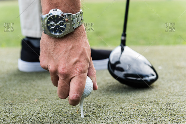 Man adjusting golf ball on tee in the golf course