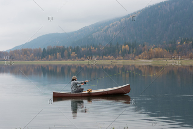 Man and dog on boat throwing fishing line in the middle of river