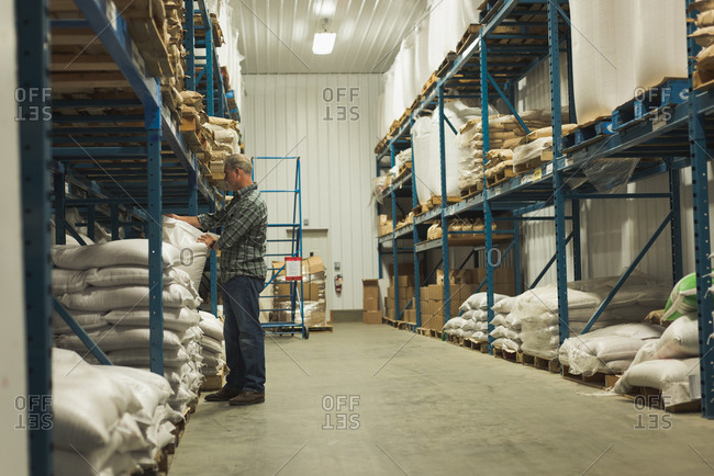 Man adjusting grain sack on shelf in factory
