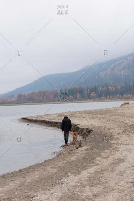 Man and his pet dog walking at river bank