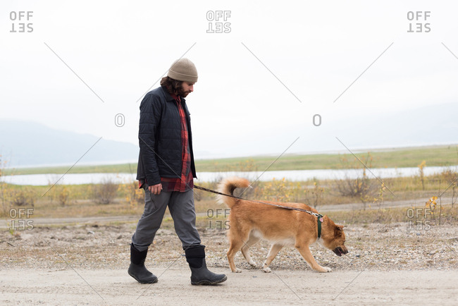 Man and his pet dog walking on empty path