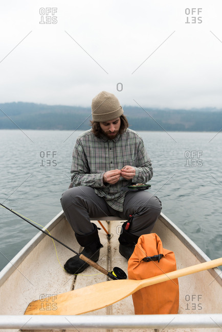 Man in boat fixing bait to the fishing line