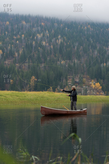 Man in canoe throwing fishing line in river beside pasture
