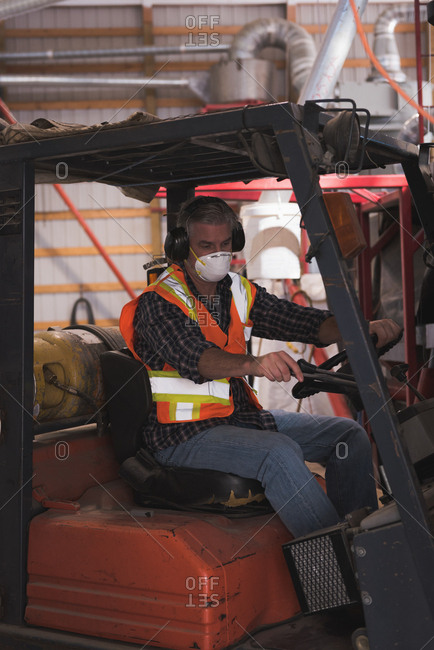 Man in protective workwear sitting in forklift at factory