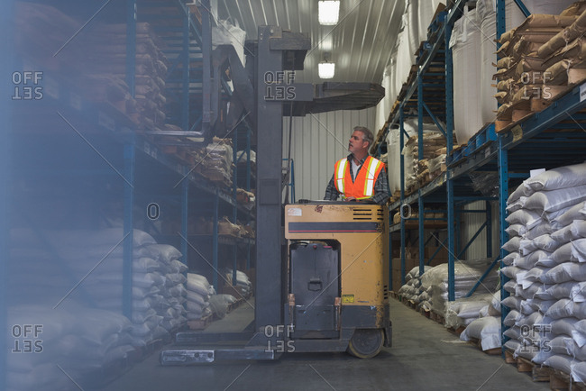 Man lifting sack of grains with forklift in factory