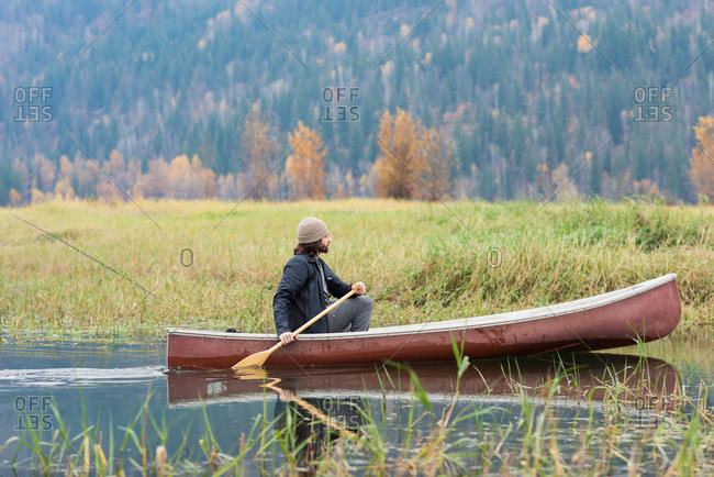 Man oaring canoe in river near grassland