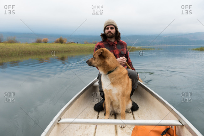 Man oaring canoe in river with his dog on board