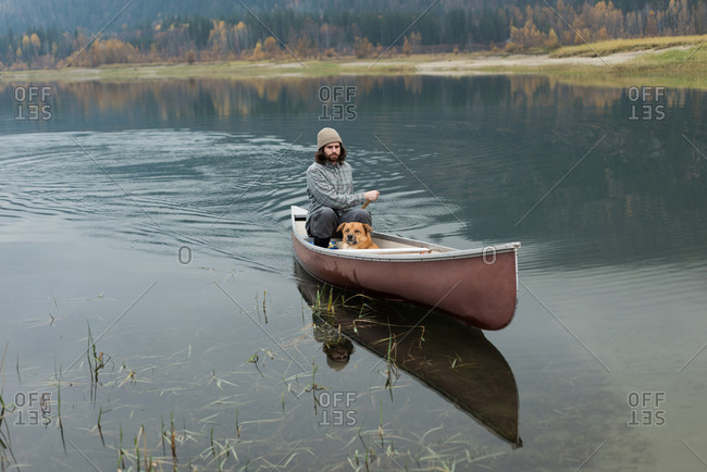 Man oaring canoe in river with his dog