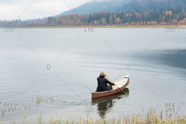 Man oaring canoe in silent river