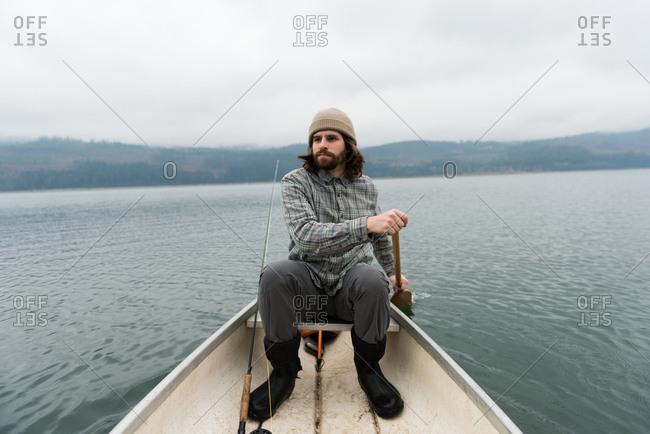 Man oaring canoe in silent river