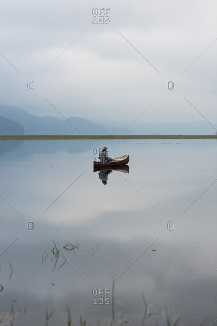 Man on boat in silent river with his reflection in water