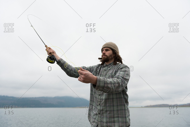 Man throwing fishing line in river on a foggy day
