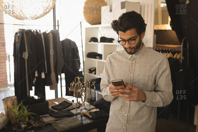 Man using mobile phone in boutique shop