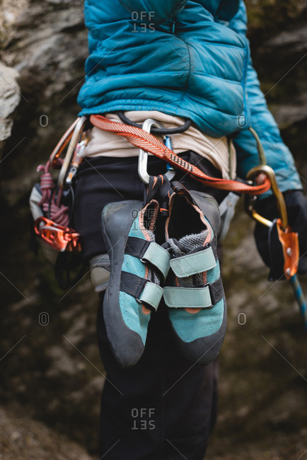 Mid section of climber standing with climbing shoes attached to harness