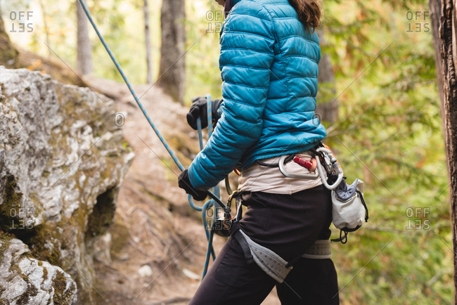 Mid section of female climber preparing herself to climb the cliff