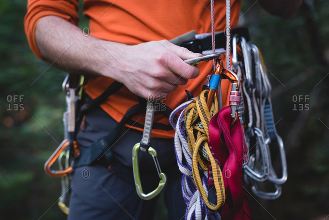 Mid section of hiker adjusting the carabineer on rope
