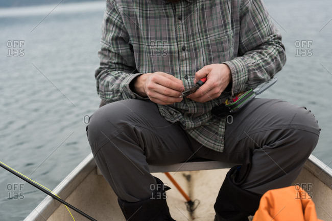 Mid section of man holding pliers in his hand at boat