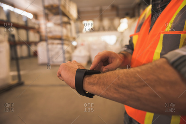 Mid section of man in protective workwear using smartwatch