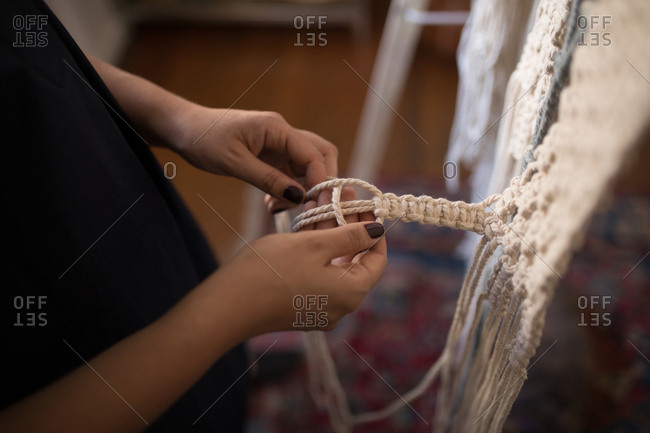 Mid section of woman knotting strings in workshop