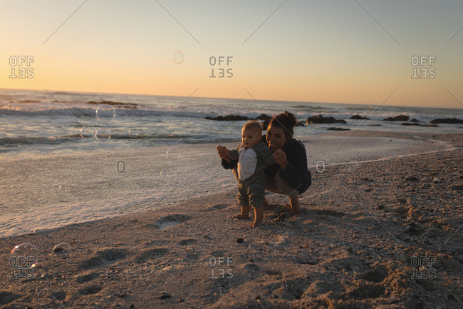 Mother and son blowing bubble with bubble wand at beach during sunset