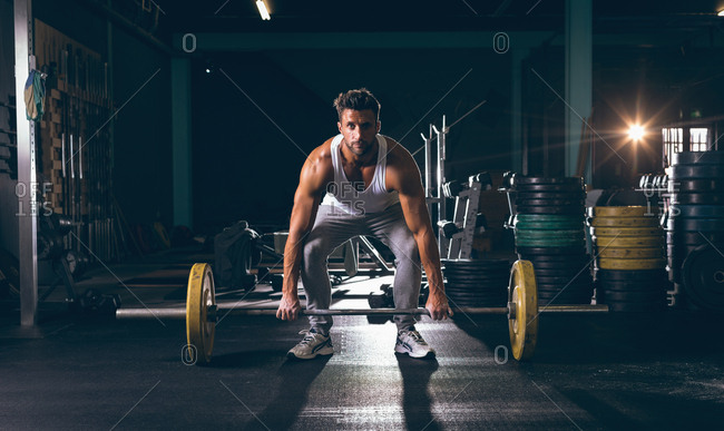 Portrait of muscular man exercising with barbell in the fitness studio