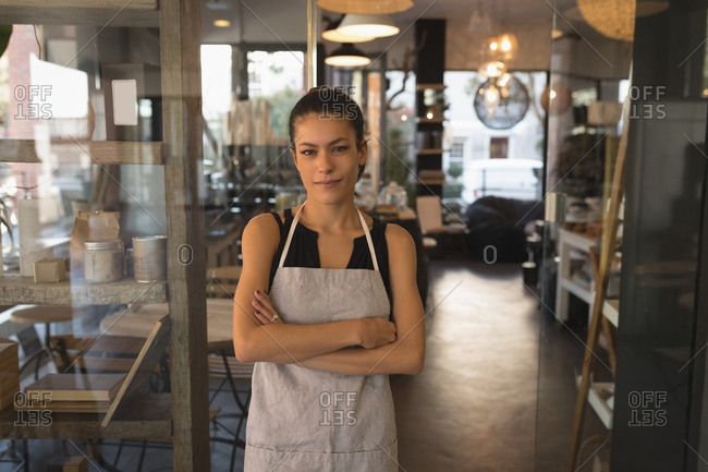 Portrait of waitress standing with arms crossed in coffee shop