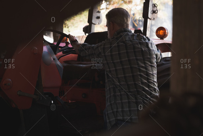 Rear view of farmer preparing to sit in tractor