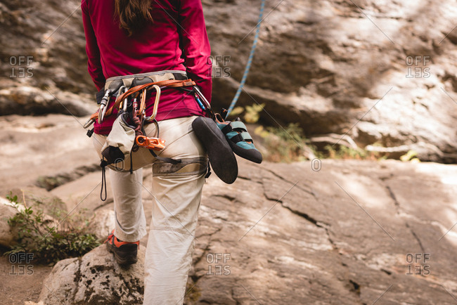 Rear view of female hiker preparing herself to climb the rocky mountain