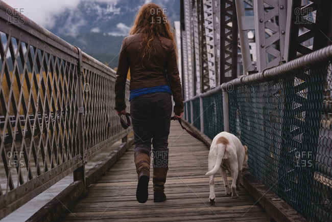 Rear view of woman walking on the bridge with her pet dog