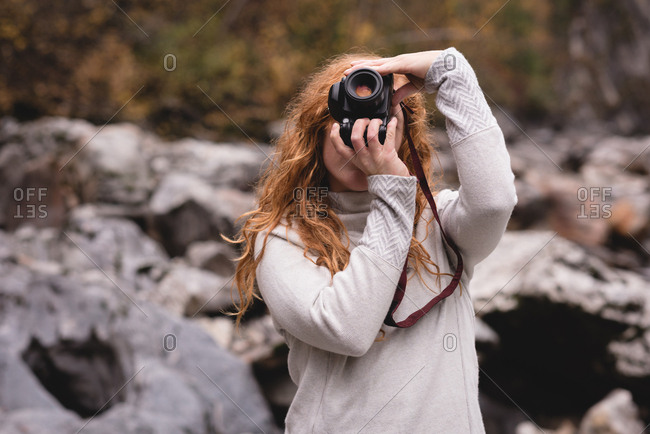 Red haired woman photographing in the forest