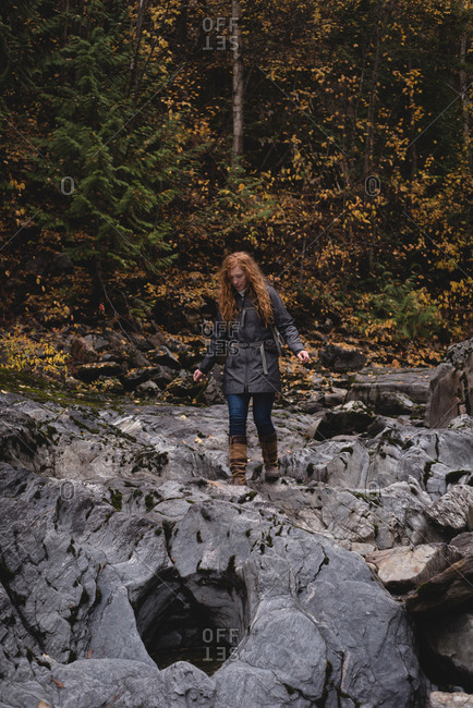 Red haired woman walking on the wet rocks