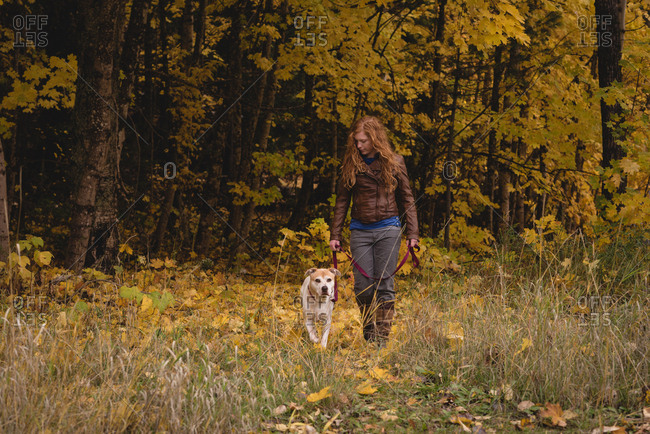 Red haired woman walking in autumn forest with pet dog