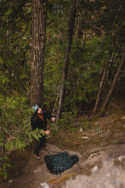 Rock climber preparing himself to climb the cliff in forest